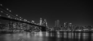 Views of Brooklyn Bridge and New York City lights at night. Black and white image