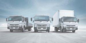 three moving trucks driving along road
